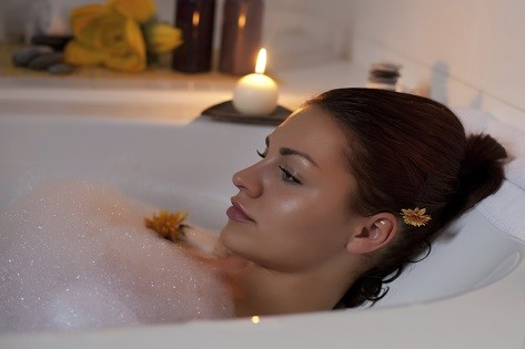 Beautiful young woman relaxing in bathtub.