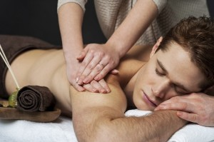 Masseur doing back massage on man body