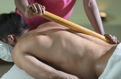 Young man receiving a bamboo massage