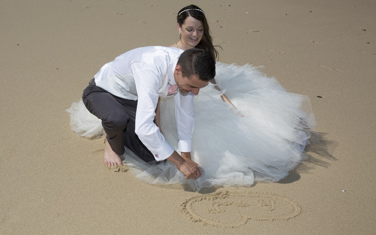 Beautiful wedding couple at the beach with wedding dress